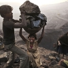 A young woman trips As She carries A large basket illegally mined coal